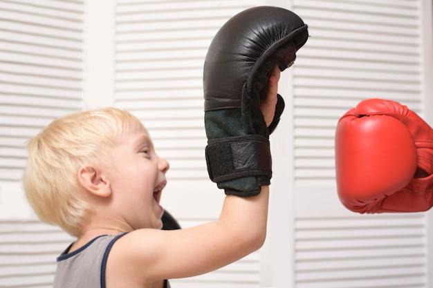 Niño rubio de boxeo con la mano en el guante rojo. emociones