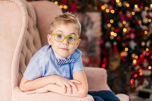 Niño rubio en camisa azul con gafas grandes sentado en la silla