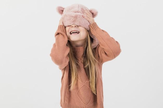 Niño rubio cubriéndose la cara con sombrero de invierno