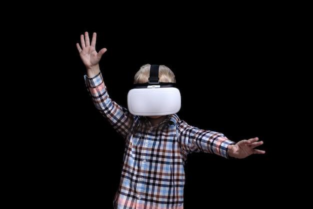Niño rubio con gafas de realidad virtual. camisa a cuadros. fondo negro