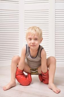 Niño rubio en guantes de boxeo rojos. relajación