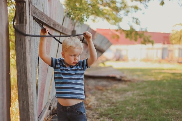 Niño rubio jugando con una cuerda colgando de una valla de madera vieja