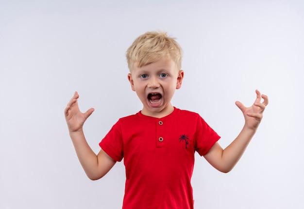 Un niño rubio lindo enojado en camiseta roja gritando con las manos en alto
