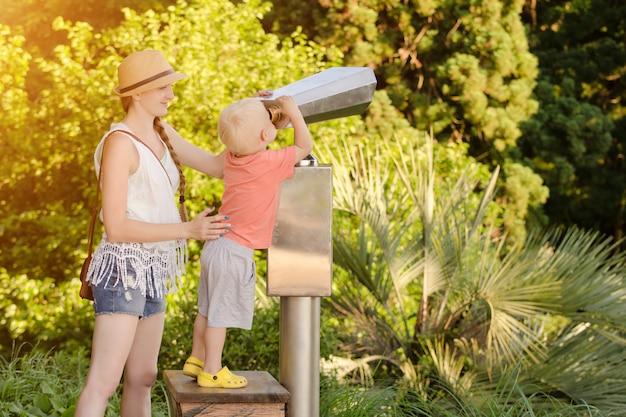 Niño rubio mirando en un gran par de binoculares con su madre