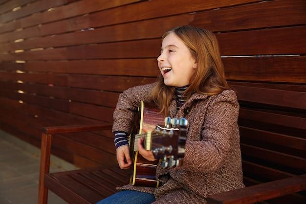 Niño rubio, niña, tocar la guitarra