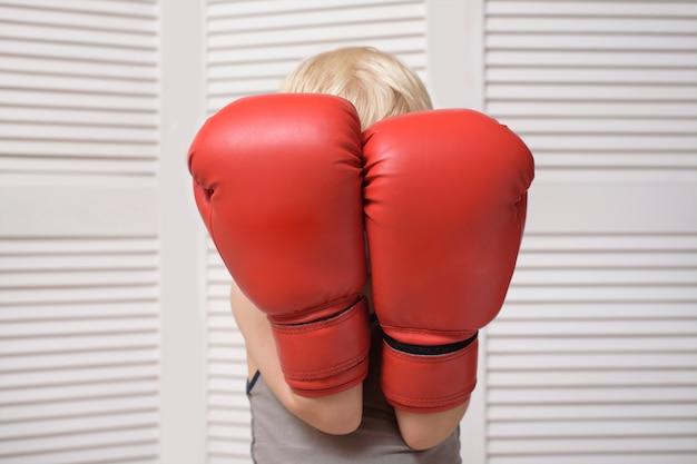 El niño rubio está protegido con dos guantes de boxeo. retrato