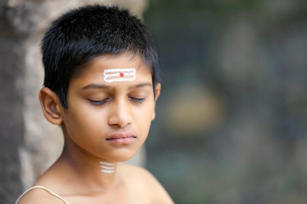 El niño sacerdote indio haciendo meditación