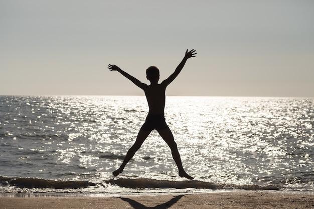 Niño saltando con brazos y piernas a los lados en la playa contra el sol