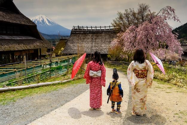 Niño samurai con espada y dos mujeres japonesas kimono en saiko iyashi no sato nenba