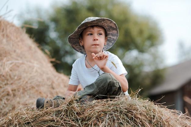 Niño sentado a la altura de un gran pajar en el pueblo. el niño el granjero.