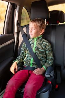 Niño sentado en un asiento elevado abrochado en el coche.