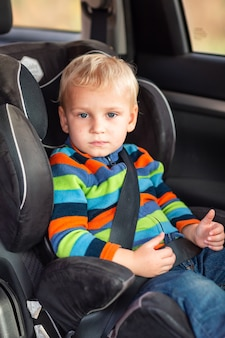 Niño sentado en un asiento de seguridad abrochado en el coche.