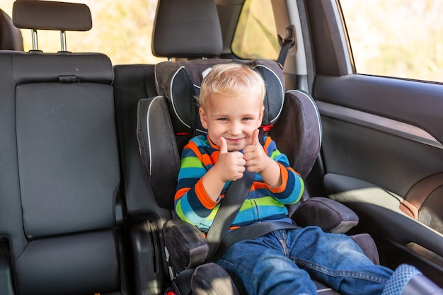 Niño sentado en un asiento de seguridad abrochado con el pulgar hacia arriba en el coche.