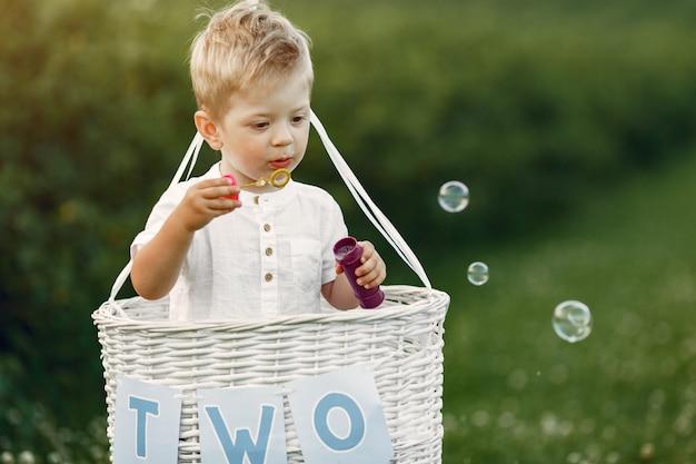 Niño sentado en la canasta con globos