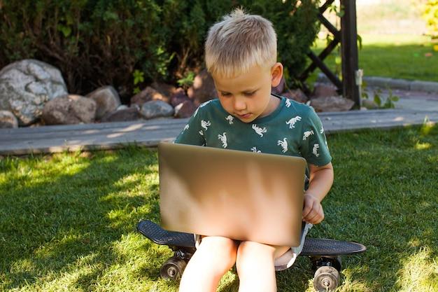 El niño está sentado en el césped y estudia en una computadora portátil. concepto de aprendizaje a distancia, aprendizaje en casa, desescolarización.