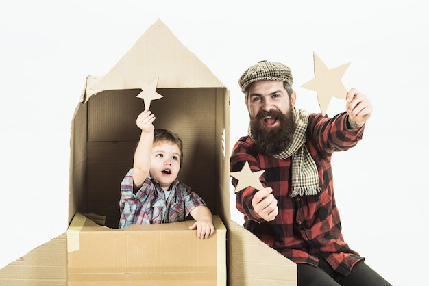 Niño sentado en el cohete espacial de cartón apunta hacia arriba por la familia feliz del día del padre estrella jugando con cartón