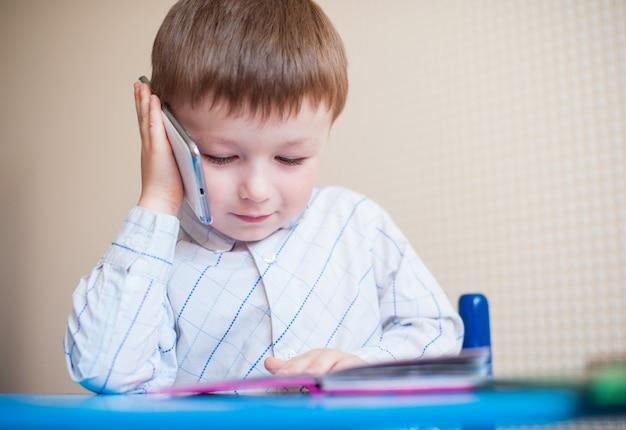 Niño sentado en el escritorio y hablando por teléfono