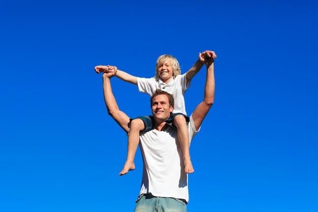 Niño sentado en los hombros de su padre