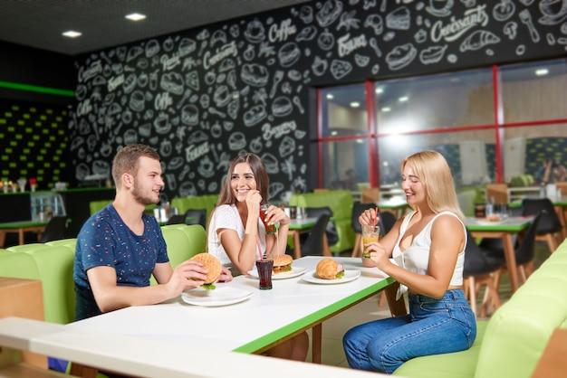 Niño sentado junto a dos niñas y hablando en la cafetería