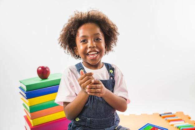 Niño sentado con libros y sonriendo en estudio