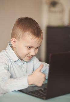 Niño sentado en la mesa y hablando en línea. escritorio de oficina con laptop. niño aprendiendo en línea. educación a distancia en línea.