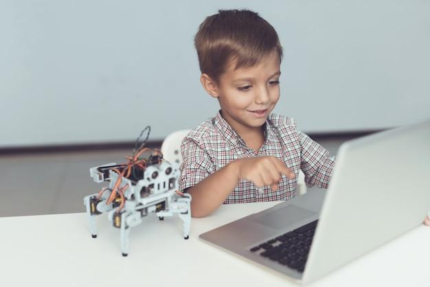 El niño está sentado a la mesa y trabajando detrás del portátil gris