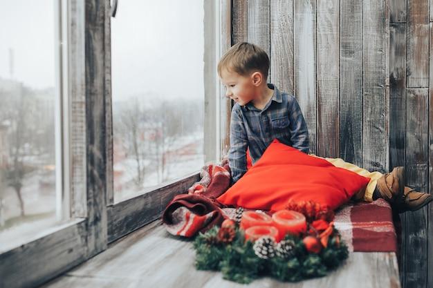 Niño sentado y mirando por la ventana