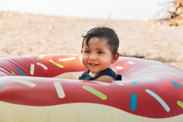 Niño sentado en la playa en círculo inflable