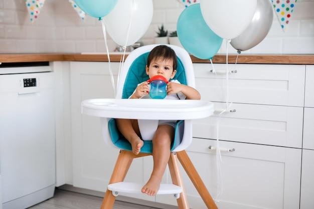 Niño sentado en la silla alta azul en casa en la cocina blanca y bebiendo agua de una taza para sorber en el fondo con globos.