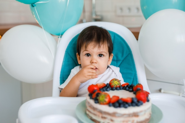 Niño sentado en la silla alta en la cocina blanca y degustación de pastel de primer año con frutas sobre fondo con globos.