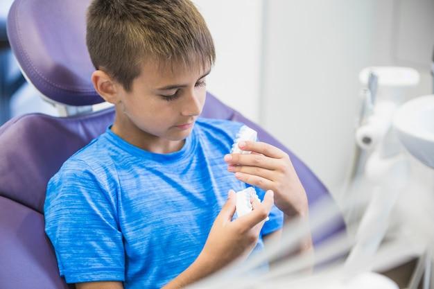 Niño sentado en la silla dental mirando los dientes yeso molde