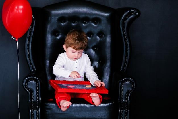 Niño sentado en el sillón con cuadro rojo enmarcado en el día de san valentín.