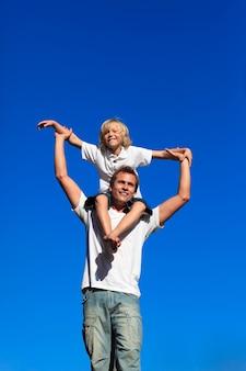 Niño sentado sobre los hombros de su padre