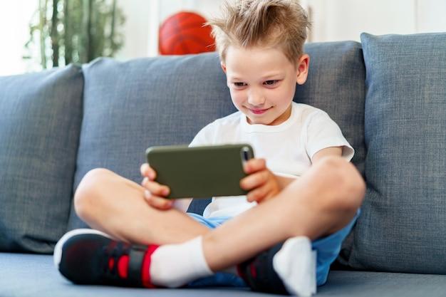 Niño sentado en el sofá en casa y con smartphone