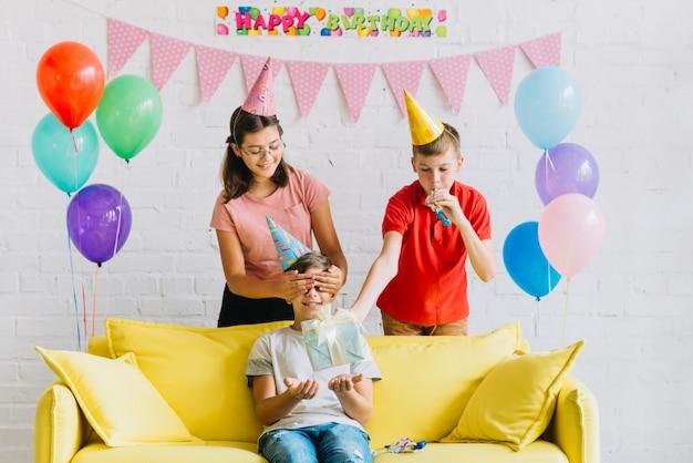 Niño sentado en el sofá recibiendo un regalo sorpresa de cumpleaños de sus amigos