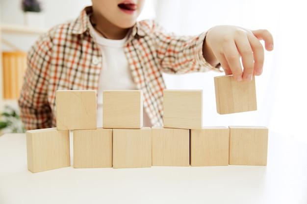 Niño sentado en el suelo. chico guapo jugando con cubos de madera en casa.