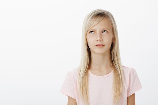 Niño serio concentrado recordando material aprendido mientras responde cerca de la pizarra en la escuela. preocupado pensando en linda chica, mirando hacia arriba y de pie sobre una pared gris recordando