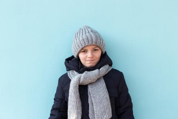 Niño serio divertido listo para las vacaciones de invierno. chico de moda en invierno gorro gris y bufanda de pie contra la pared azul.