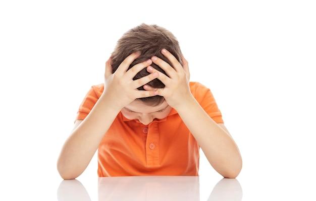 Un niño serio en edad escolar con una camiseta polo naranja brillante se sienta en una mesa y se agarra la cabeza con las manos. la desesperación y la falta de ayuda. isolirvoan sobre un fondo blanco.
