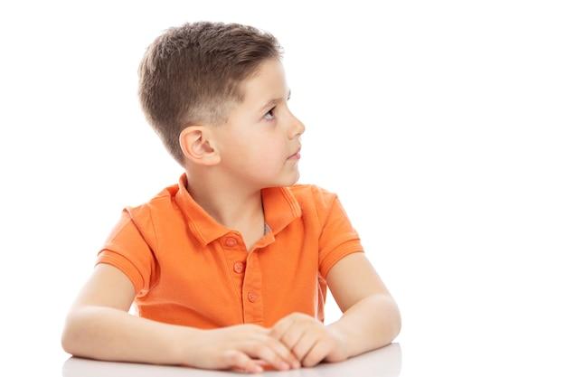 Un niño serio en edad escolar con una camiseta polo naranja brillante se sienta en una mesa y mira a un lado. isolirvoan sobre un fondo blanco.
