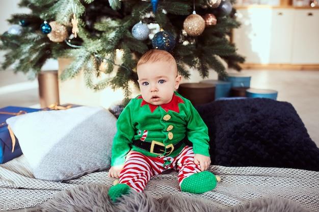 Niño se sienta en un árbol de navidad