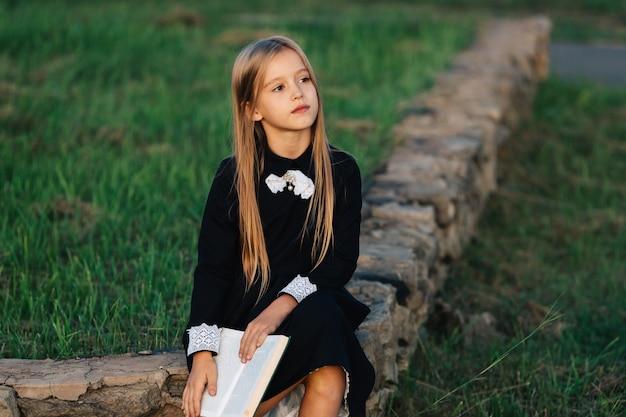 El niño se sienta en un banco de piedra, sostiene un libro en sus manos y mira a lo lejos.