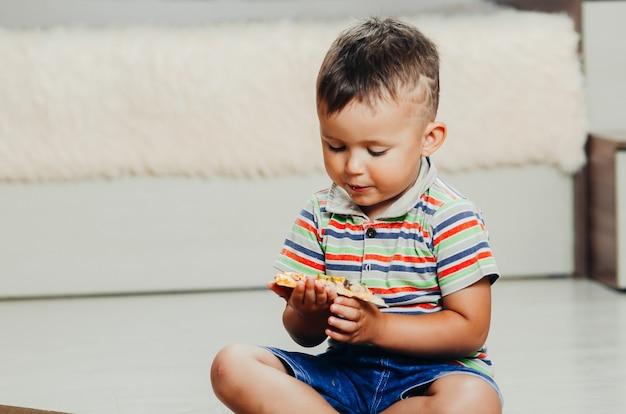 El niño se sienta en el suelo y come pizza muy apetecible y codicioso, en pantalón corto y camiseta