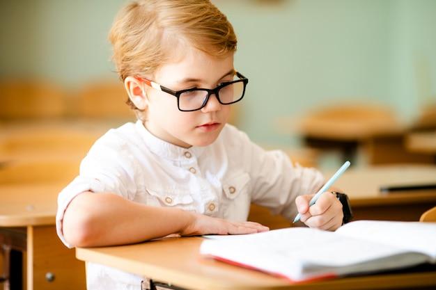 Niño de siete años con gafas escribiendo su tarea en la escuela