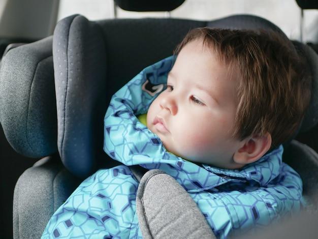 Niño en una silla de auto. seguridad infantil en el asiento de seguridad para niños durante el sueño.