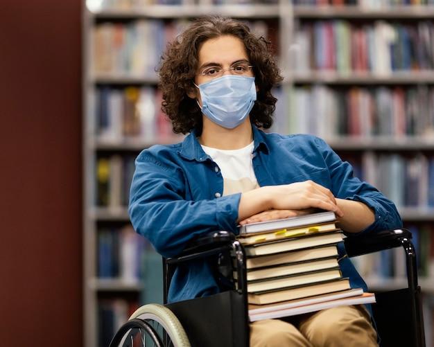 Niño en silla de ruedas sosteniendo un montón de libros