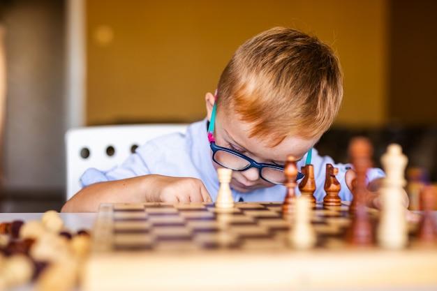 Niño con síndrome de down con gafas grandes jugando al ajedrez.