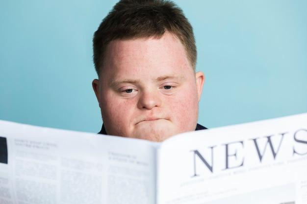 Niño con síndrome de down leyendo un periódico durante la pandemia de coronavirus