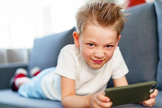 Niño con smartphone mientras está acostado en el sofá en casa, retrato
