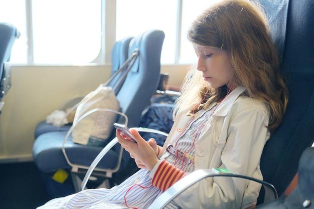 Niño con smartphone mientras está sentado dentro del ferry